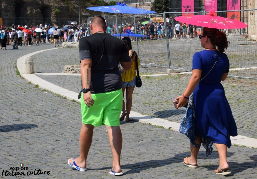 Parasols keep this couple shaded from the heat of Rome in summer.