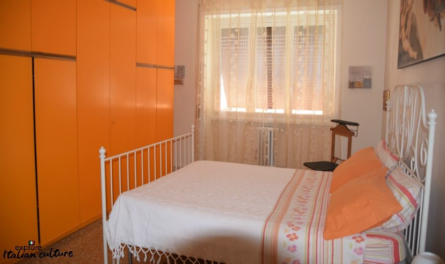Laura's apartment in Rome: the bedroom, with queen sized bed and orange wardrobes.