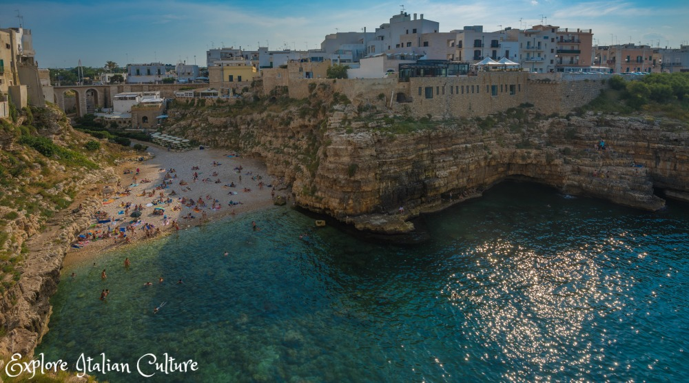 The beach at Polignano a Mare, Puglia, Italy - formed by a break in two rock faces and surrounded by the town of Polignano itself.