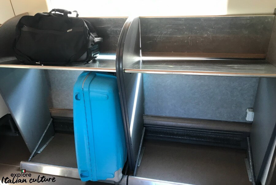 Luggage on an inter-city Italian train, stored in a rack at the end of a carriage.