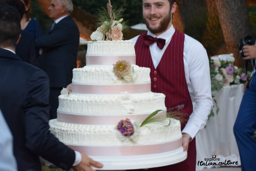 An Italian wedding cake being carried by two waiters.