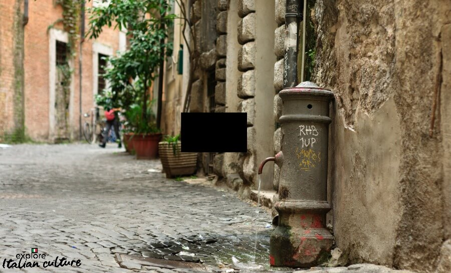 Old drinking fountain in public street, Rome.