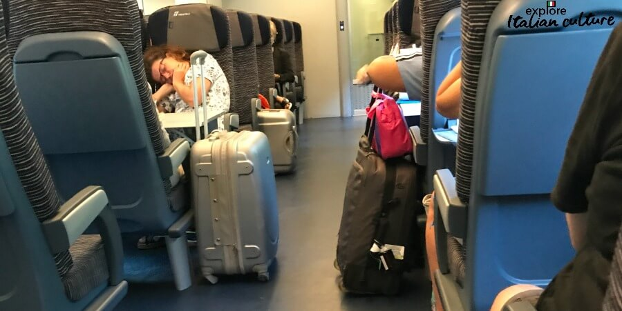 Luggage kept in the aisle of a local train in Italy.